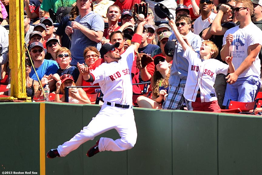 """Boston Red Sox right fielder Shane Victorino leaps the wall as he attempts to make a catch during the third inning of a game against the Arizona Diamondbacks Sunday, August 4, 2013 at Fenway Park in Boston, Massachusetts."""