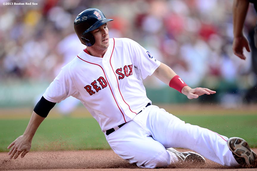 """Boston Red Sox shortstop Stephen Drew slides into third base on a hit and run play during the fifth inning of a game against the Arizona Diamondbacks Sunday, August 4, 2013 at Fenway Park in Boston, Massachusetts."""