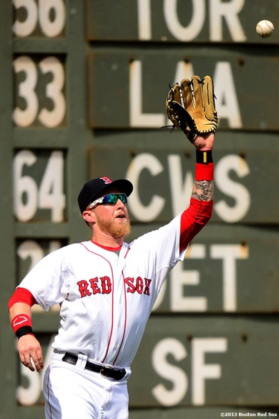 """Boston Red Sox left fielder Mike Carp catches a fly ball during the sixth inning of a game against the Arizona Diamondbacks Sunday, August 4, 2013 at Fenway Park in Boston, Massachusetts."""