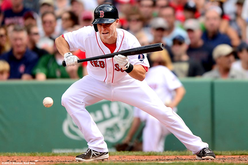 """Boston Red Sox third baseman Brock Holt lays down a bunt during the seventh inning of a game against the Arizona Diamondbacks Sunday, August 4, 2013 at Fenway Park in Boston, Massachusetts."""