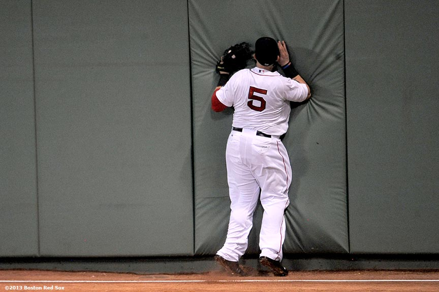 """Boston Red Sox outfielder Jonny Gomes runs into the wall after fielding a base hit during the third inning of a game against the Baltimore Orioles Tuesday, August 27, 2013 at Fenway Park in Boston, Massachusetts."""