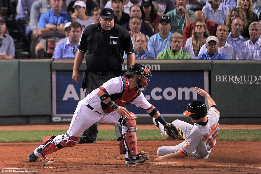"""Boston Red Sox catcher Jarrod Saltalamacchia applies a tag on Danny Valencia as he tags up at home plate during the third inning inning of a game against the Baltimore Orioles Tuesday, August 27, 2013 at Fenway Park in Boston, Massachusetts."""