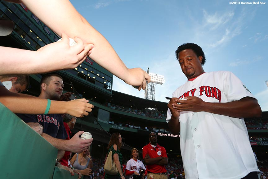 """Former Boston Red Sox pitcher Pedro Martinez signs autographs for fans before a Jimmy Fund pre-game ceremony Wednesday, August 28, 2013 at Fenway Park in Boston, Massachusetts."""