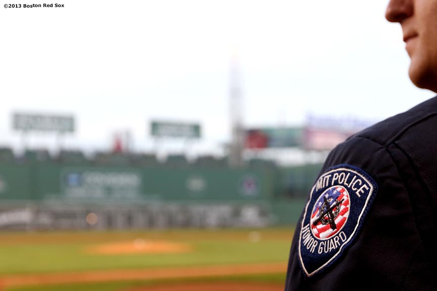 """An member of the MIT Color Guard stands on the field Wednesday, August 28, 2013 at Fenway Park in Boston, Massachusetts before a ceremonial first pitch ceremony honoring Sean Collier, an MIT Police Officer who was killed during the Boston Marathon attacks."""