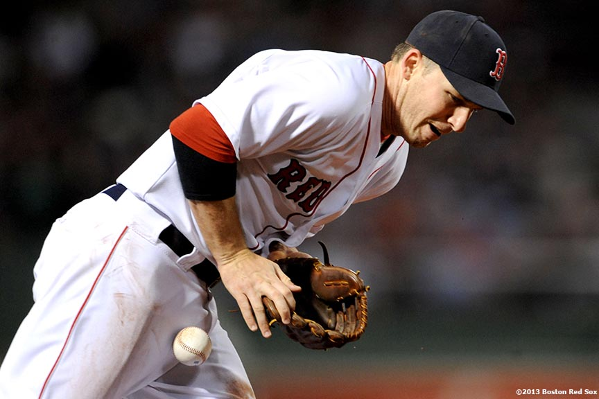 """Boston Red Sox shortstop Stephen Drew bobbles a ground ball during the third inning of a game against the Baltimore Orioles Thursday, August 29, 2013 at Fenway Park in Boston, Massachusetts."""