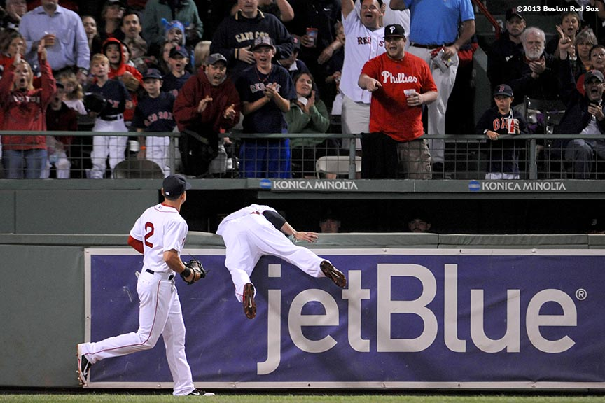 """Boston Red Sox outfielder Shane Victorino leaps over the outfield wall after making a catch during the third inning of a game against the Baltimore Orioles Thursday, August 29, 2013 at Fenway Park in Boston, Massachusetts."""