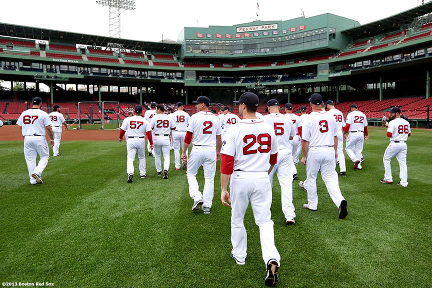 """The Boston Red Sox walk toward the dugout after posing for the official team photograph Thursday, August 29, 2013 at Fenway Park in Boston, Massachusetts."""