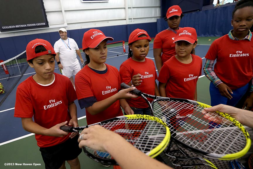 """Kids are given racquets during an Emirates Airline tennis clinic on Day 7 of the New Haven Open at Yale University in New Haven, Connecticut Thursday, August 20, 2013."""