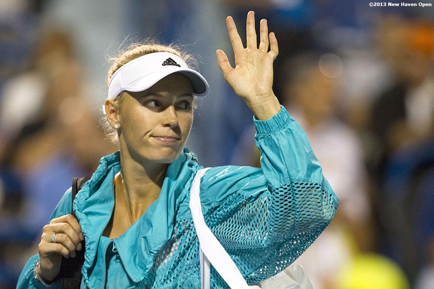 """Caroline Wozniacki waves to the crowd as she walks off Stadium Court after losing in the semi-finals to Simon Halep on Day 8 of the New Haven Open at Yale University in New Haven, Connecticut Friday, August 20, 2013."""