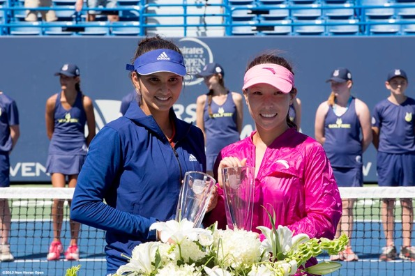 """Sania Mirza and Jie Zheng pose with the trophies after winning the doubles title at the New Haven Open at Yale University in New Haven, Connecticut Saturday, August 24, 2013."""