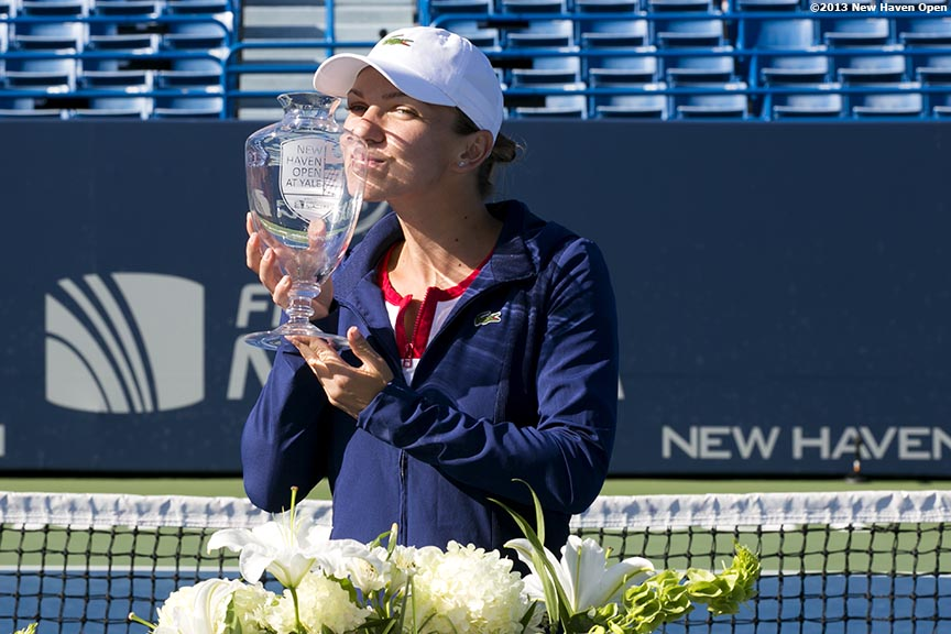 """Simona Halep kisses the trophy after defeating Petra Kvitova in the finals to win the New Haven Open at Yale University in New Haven, Connecticut Saturday, August 24, 2013."""