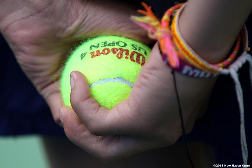 """A ball girl holds a tennis ball behind her back on Day 2 of the New Haven Open at Yale University in New Haven, Connecticut Saturday, August 17, 2013."""
