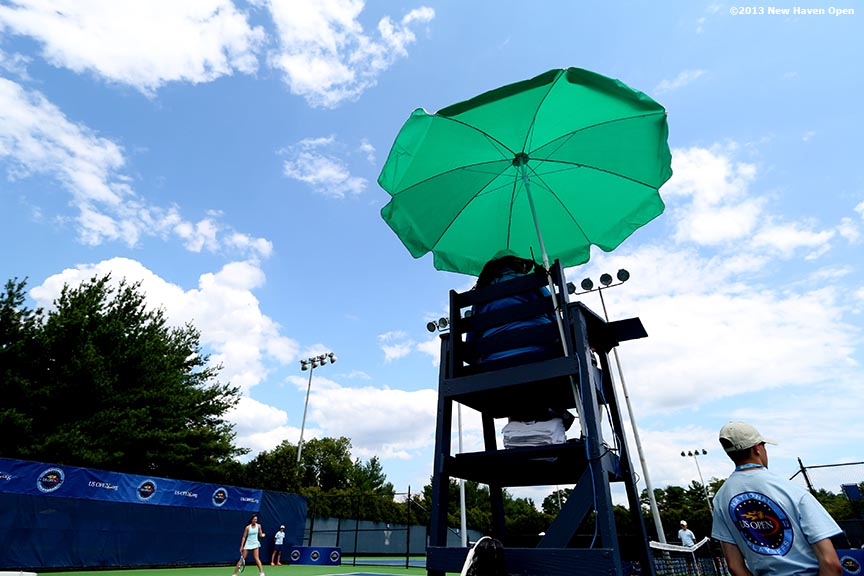 """A chair umpire sits under an umbrella on Day 1 of the New Haven Open at Yale University in New Haven, Connecticut Friday, August 16, 2013."""