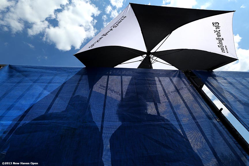 """Fans sit under an umbrella as they watch a match on Day 2 of the New Haven Open at Yale University in New Haven, Connecticut Saturday, August 17, 2013."""