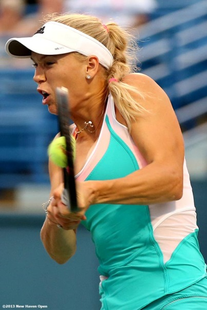"""Caroline Wozniacki connects on a forehand during her semi-final match against Simona Halep on Day 8 of the New Haven Open at Yale University in New Haven, Connecticut Friday, August 20, 2013."""