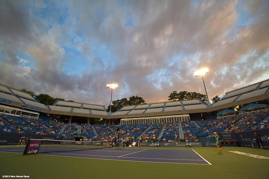 """The sun sets as Caroline Wozniacki and Simona Halep play in a semi-final match on Stadium Court on Day 8 of the New Haven Open at Yale University in New Haven, Connecticut Friday, August 20, 2013."""
