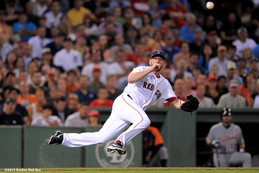 """Boston Red Sox pitcher Ryan Dempster falls as he throws to first base after fielding a bunt during the fourth inning of a game against the Detroit Tigers Wednesday, September 4, 2013 at Fenway Park in Boston, Massachusetts."""