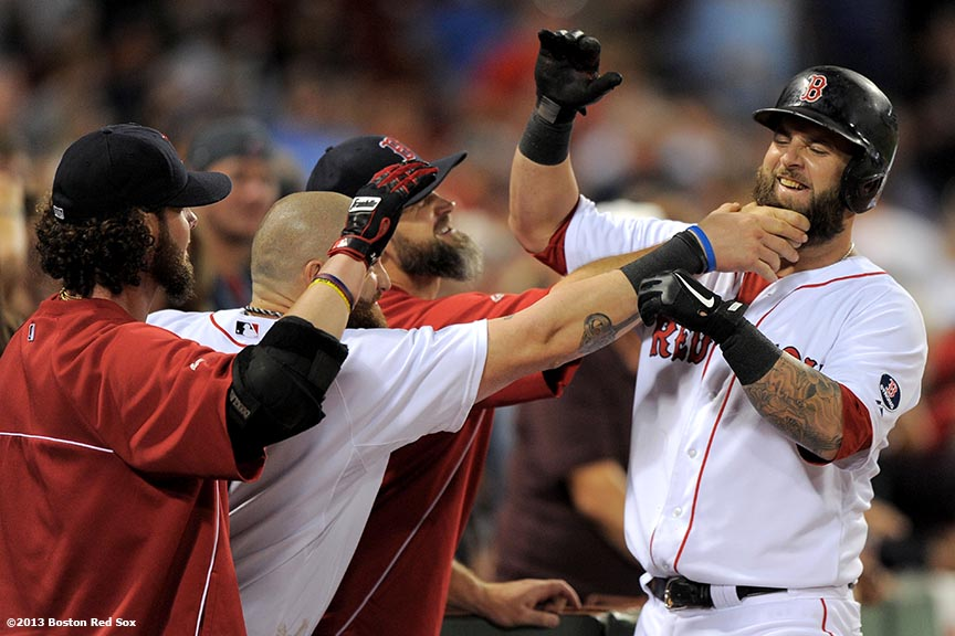 """Boston Red Sox teammates playfully tug on the beard of first baseman Mike Napoli after scoring a run during the eighth inning of a game against the Detroit Tigers Wednesday, September 4, 2013 at Fenway Park in Boston, Massachusetts."""