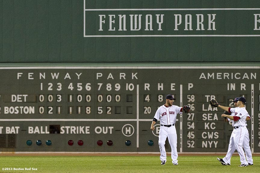 """Boston Red Sox outfielders  Mike Carp, Daniel Nava, and Jacoby Ellsbury celebrate in front of the Green Monster scoreboard after the Red Sox defeated the Detroit Tigers 20-4 on 19 hits and a franchise record-tying eight home runs Wednesday, September 4, 2013 at Fenway Park in Boston, Massachusetts."""