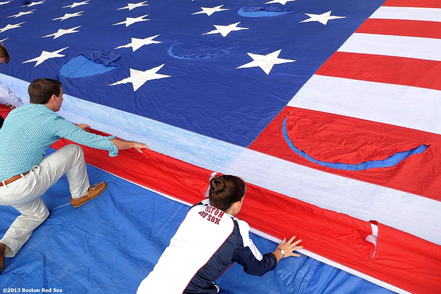 """Members of the Boston Red Sox Front Office help roll an American Flag in preparation for a 9/11 memorial flag drop over the Green Monster Friday, September 13, 2013 at Fenway Park in Boston, Massachusetts."""