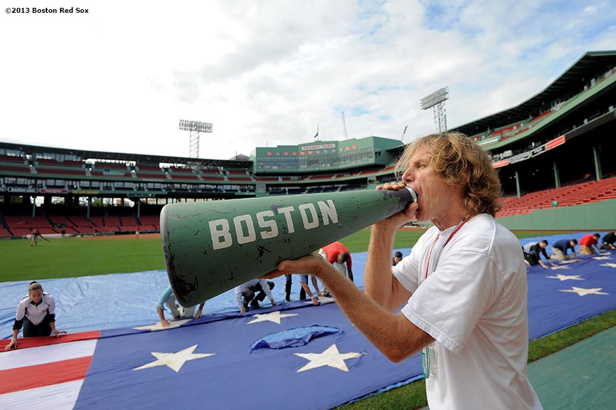 """John Coyne, US Flag Coordinator of the Boston Red Sox, gives instructions as members of the Red Sox Front Office help roll an American Flag in preparation for a 9/11 memorial flag drop over the Green Monster Friday, September 13, 2013 at Fenway Park in Boston, Massachusetts."""