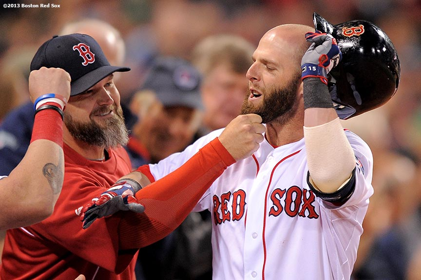 """Boston Red Sox catcher David Ross playfully tugs on the beard of second baseman Dustin Pedroia after Pedroia hit a solo home run during the first inning of a game against the Baltimore Orioles Tuesday, September 7, 2013 at Fenway Park in Boston, Massachusetts."""