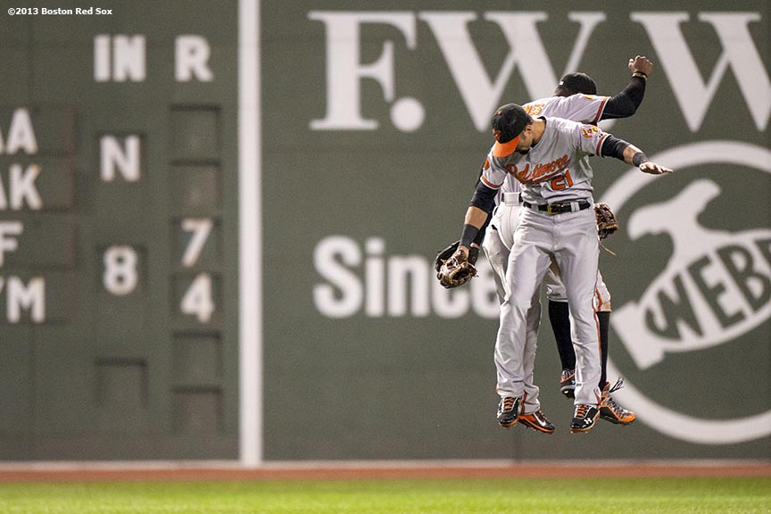 """Baltimore Orioles outfielders Nick Markakis, Adam Jones, and Nate McLouth celebrate in center field after defeating the Boston Red Sox Tuesday, September 7, 2013 at Fenway Park in Boston, Massachusetts."""