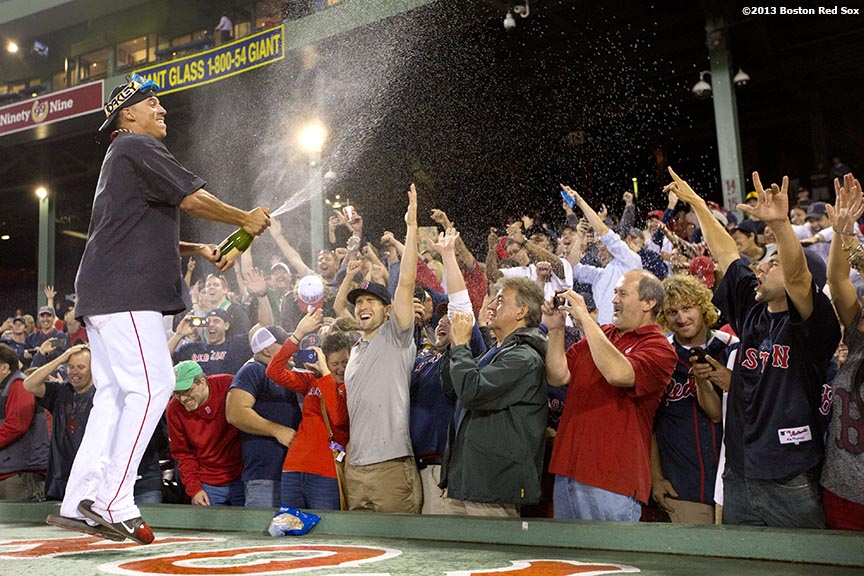 """Boston Red Sox outfielder Quintin Berry sprays fans with champagne on top of the dugout during an on-field celebration after the Red Sox clinched the American League East title with a 6-3 win over the Toronto Blue Jays Friday, September 20, 2013 at Fenway Park."""
