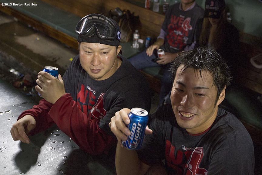 """Boston Red Sox pitchers Junichi Tazawa and Koji Uehara drink beer in the dugout during an on-field celebration after the Red Sox clinched the American League East title with a 6-3 win over the Toronto Blue Jays Friday, September 20, 2013 at Fenway Park."""