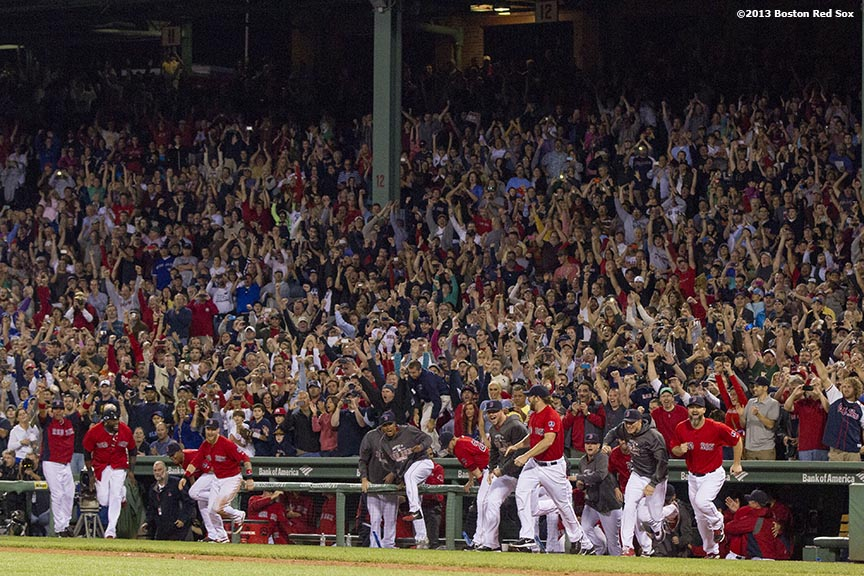 """Boston Red Sox teammates run out of the dugout in celebration after recording the final out of a 6-3 win over the Toronto Blue Jays to clinch the American League East title at Fenway Park Friday, September 23, 2013."""