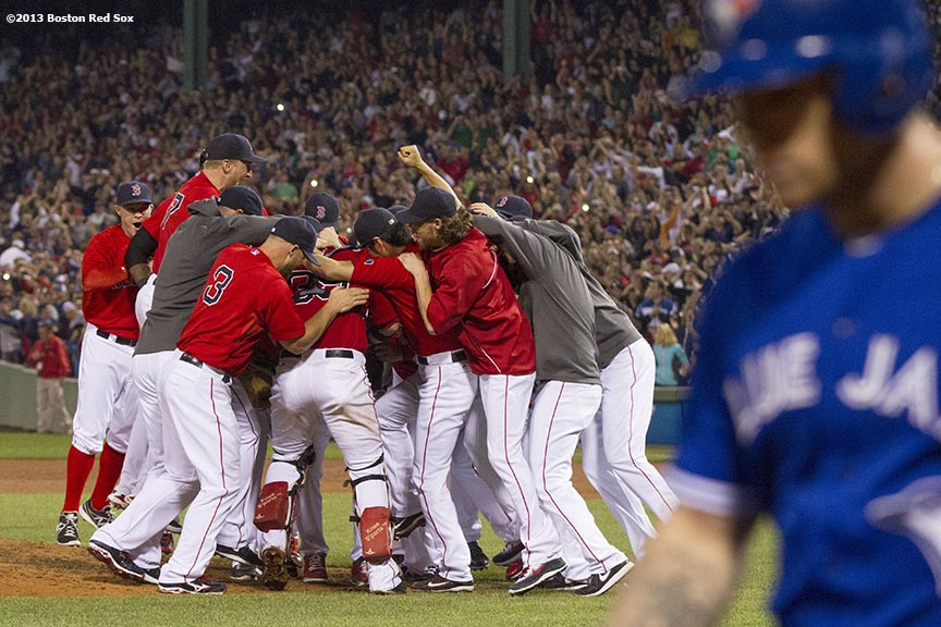 """Boston Red Sox teammates celebrate on the field after recording the final out of a 6-3 win over the Toronto Blue Jays to clinch the American League East title at Fenway Park Friday, September 20, 2013."""