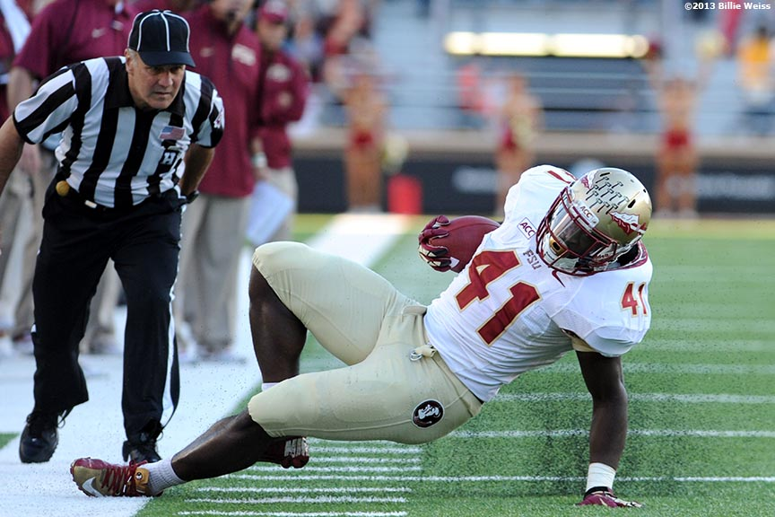 """Florida State Seminoles fullback Chad Abram slips along the sideline after a carry during the third quarter of a game against the Boston College Eagles at Alumni Stadium in Chestnut Hill, Massachusetts Saturday, September 28, 2013."""