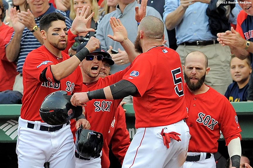 """Boston Red Sox teammates Jacoby Ellsbury, Daniel Nava, and Dustin Pedroia congratulate left fielder Jonny Gomes after scoring during the fourth inning of Game One of the American League Division Series against the Tampa Bay Rays Friday, October 4, 2013 at Fenway Park in Boston, Massachusetts."""