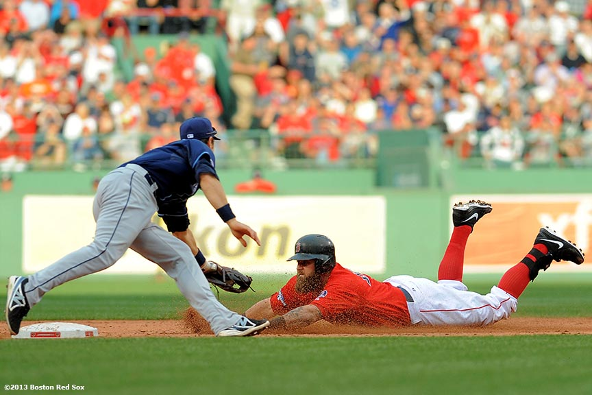 """Boston Red Sox first baseman Mike Napoli slides into second base as he avoids a tag from second baseman Ben Zobrits after hitting a double during the fifth inning of Game One of the American League Division Series against the Tampa Bay Rays Friday, October 4, 2013 at Fenway Park in Boston, Massachusetts."""