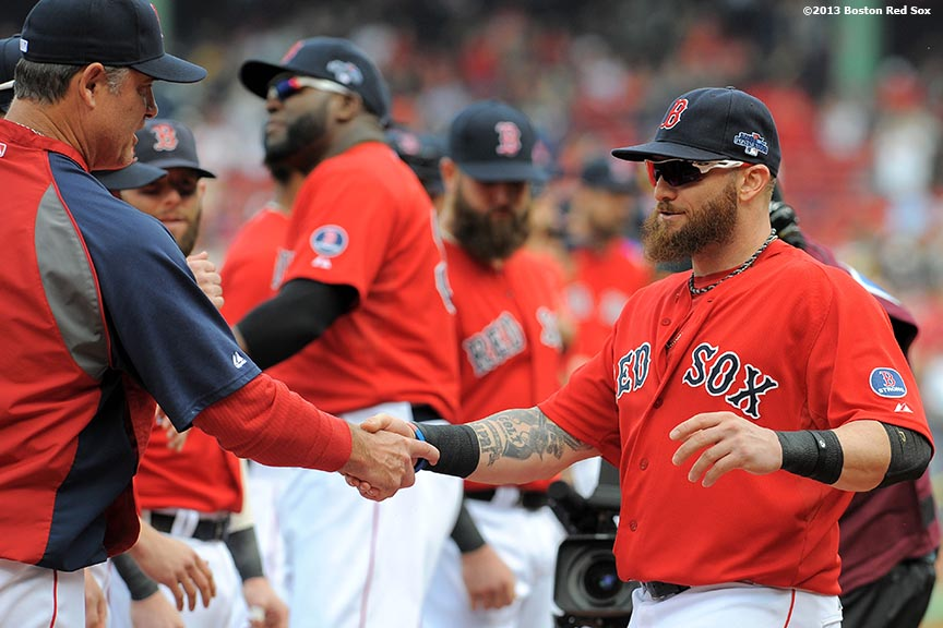 """Boston Red Sox outfielder Jonny Gomes high fives teammates during a pre-game ceremony before the first game of the American League Division Series between the Boston Red Sox and the Tampa Bay Rays Friday, October 4, 2013 at Fenway Park in Boston, Massachusetts."""