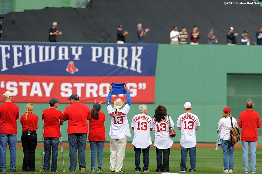 """""""Boston Marathon hero Carlos Arredondo and family members of Krystle Campbell, a victim killed in the Boston Marathon bombings, are introduced during a marathon tribute pre-game ceremony before the first game of the American League Division Series between the Boston Red Sox and the Tampa Bay Rays Friday, October 4, 2013 at Fenway Park in Boston, Massachusetts."""""""