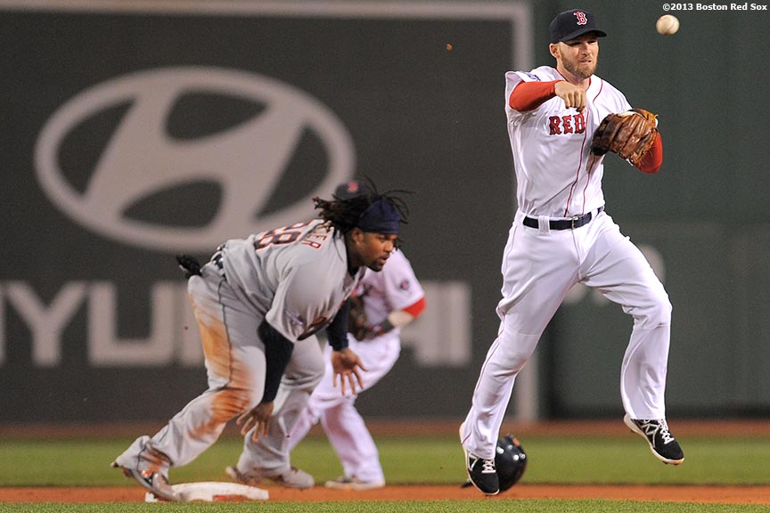 """Boston Red Sox shortstop Stephen Drew turns a double play during the third inning game one of the American League Championship Series against the Detroit Tigers Saturday, October 12, 2013 at Fenway Park in Boston, Massachusetts."""