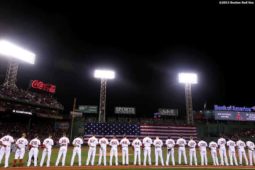 """The National Anthem is sung as teams line up during a pre-game ceremony before game one of the American League Championship Series between the Boston Red Sox and the Detroit Tigers Saturday, October 12, 2013 at Fenway Park in Boston, Massachusetts."""