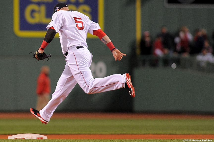 """Boston Red Sox left fielder Jonny Gomes hops over second base during the first inning of game two of the American League Championship Series against the Detroit Tigers Sunday, October 13, 2013 at Fenway Park in Boston, Massachusetts."""
