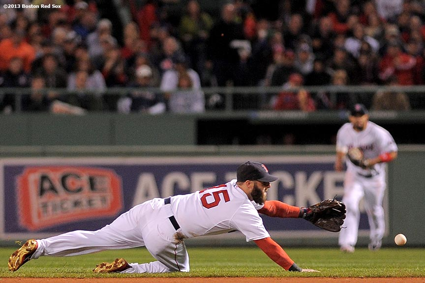 """Boston Red Sox second baseman Dustin Pedroia makes a diving stop on a ground ball during the third inning of game two of the American League Championship Series against the Detroit Tigers Sunday, October 13, 2013 at Fenway Park in Boston, Massachusetts."""