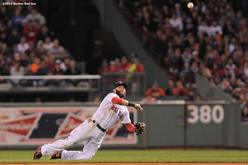 """Boston Red Sox second baseman Dustin Pedroia throws to first base after making a diving stop on a ground ball during the third inning of game two of the American League Championship Series against the Detroit Tigers Sunday, October 13, 2013 at Fenway Park in Boston, Massachusetts."""