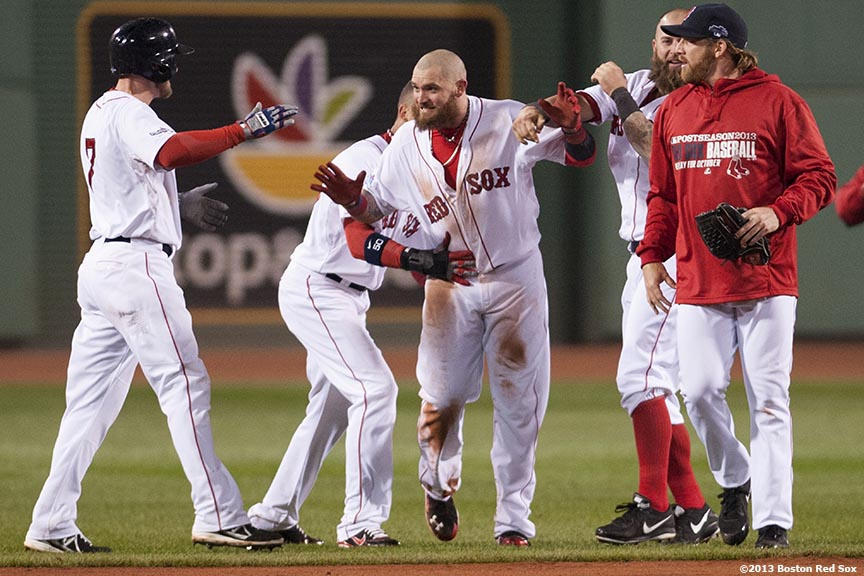 """Boston Red Sox left fielder Jonny Gomes high fives teammates after catcher Jarrod Saltalamacchia hit a game-winning RBI single during the ninth inning of game two of the American League Championship Series against the Detroit Tigers Sunday, October 13, 2013 at Fenway Park in Boston, Massachusetts."""