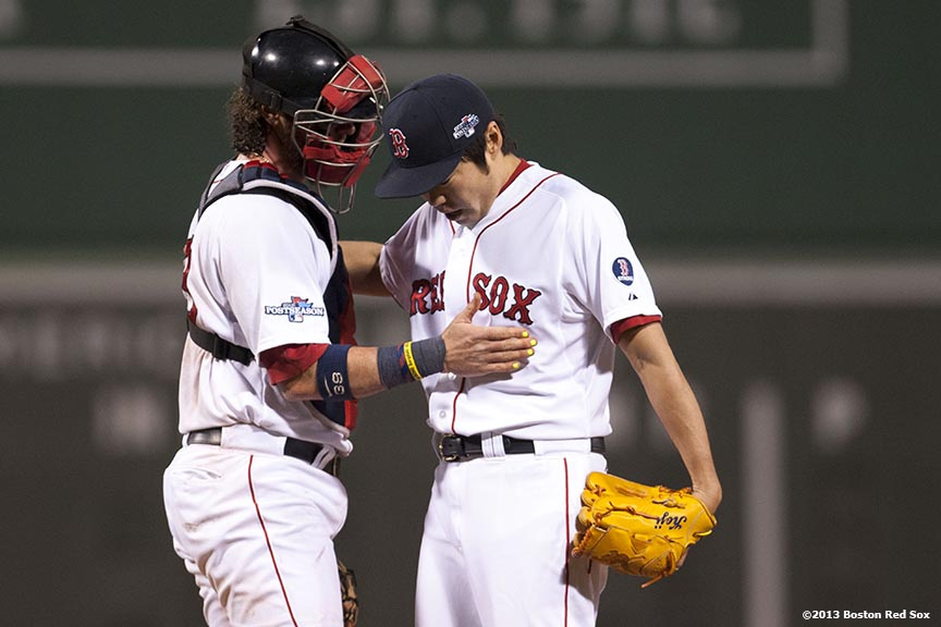 """Boston Red Sox catcher Jarrod Saltalamacchia chats with pitcher Koji Uehara during the ninth inning of game six of the American League Championship Series against the Detroit Tigers Saturday, October 19, 2013 at Fenway Park in Boston, Massachusetts."""