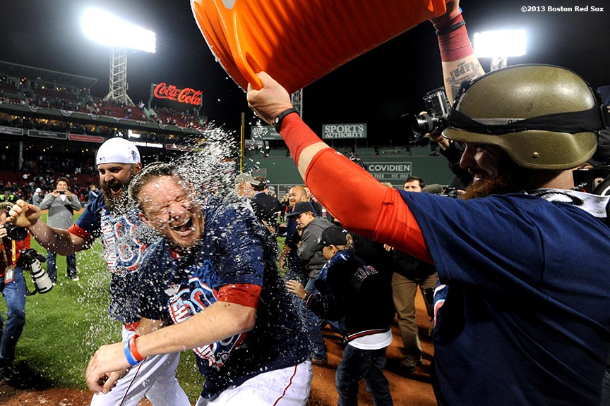 """Boston Red Sox first baseman Mike Napoli and outfielder Jonny Gomes give an ice bath to pitcher Jake Peavy during an on-field celebration after winning game six of the American League Championship Series against the Detroit Tigers and advancing to the World Series Saturday, October 19, 2013 at Fenway Park in Boston, Massachusetts."""