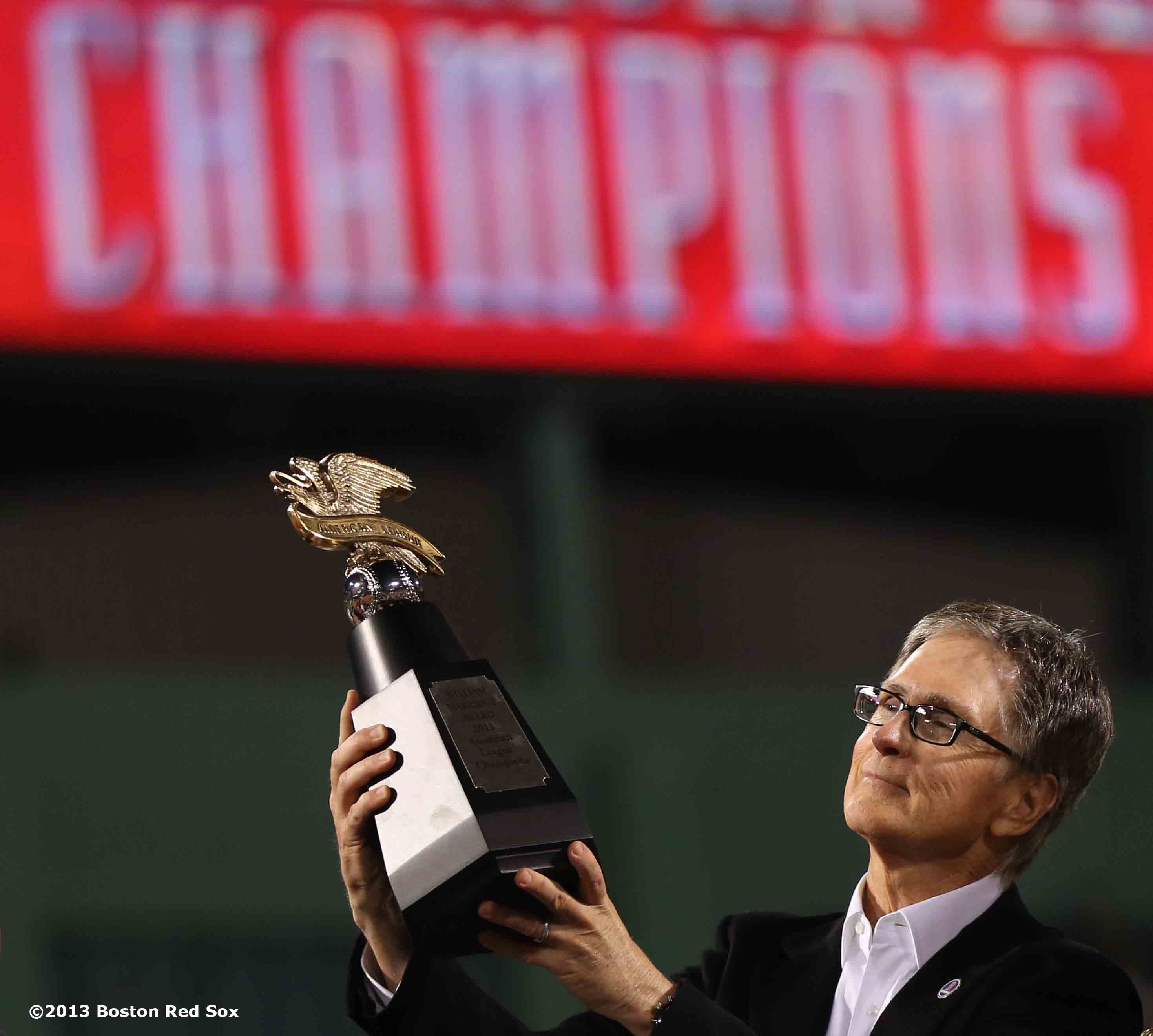 """""""Boston Red Sox Principal Owner John Henry is presented with the League Championship trophy during an on-field celebration after winning game six of the American League Championship Series against the Detroit Tigers and advancing to the World Series Saturday, October 19, 2013 at Fenway Park in Boston, Massachusetts."""""""