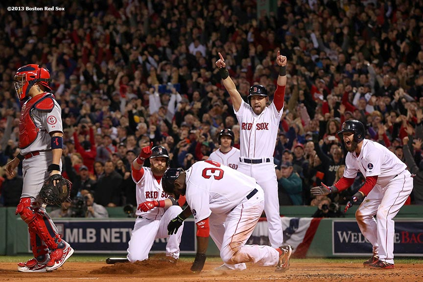 """Boston Red Sox designated hitter David Ortiz slides into home plate as right fielder Jonny Gomes, center fielder Jacoby Ellsbury, and second baseman Dustin Pedroia celebrate after scoring on a double by first baseman Mike Napoli during the first inning of game one of the 2013 World Series against the St. Louis Cardinals Wednesday, October 23, 2013 at Fenway Park in Boston, Massachusetts."""