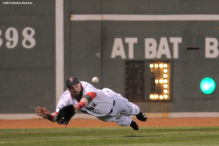 """Boston Red Sox left fielder Jonny Gomes makes a diving catch during the first inning of game two of the 2013 World Series between against the St. Louis Cardinals Thursday, October 24, 2013 at Fenway Park in Boston, Massachusetts."""