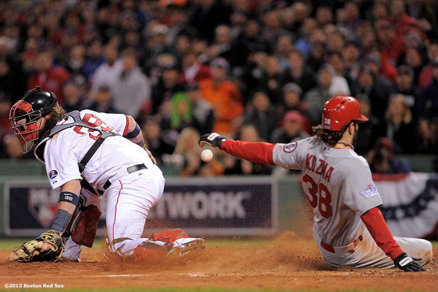 """Boston Red Sox catcher Jarrod Satlalamacchia attempts to tag out shortstop Pete Kozma during the seventh inning of game two of the 2013 World Series between against the St. Louis Cardinals Thursday, October 24, 2013 at Fenway Park in Boston, Massachusetts."""