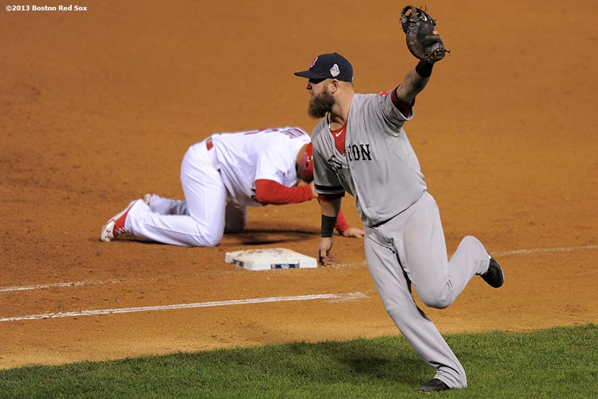 """Boston Red Sox first baseman Mike Napoli celebrates as he records the final out of game four of the 2013 World Series by tagging out St. Louis Cardinals pinch runner Kolten Wong on a pick-off throw from pitcher Koji Uehara during the ninth inning Sunday, October 27, 2013 at Busch Stadium in St. Louis, Missouri."""