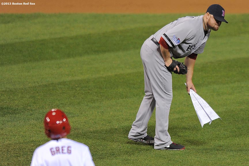 """Boston Red Sox pitcher Jon Lester picks up a paper airplane thrown on the field by a fan during the seventh inning of game five of the 2013 World Series against the St. Louis Cardinals Monday, October 28, 2013 at Busch Stadium in St. Louis, Missouri."""